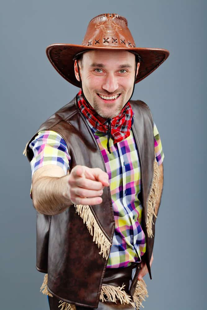 This is a man wearing a brown leather cowboy hat with his leather outfit that has frills.