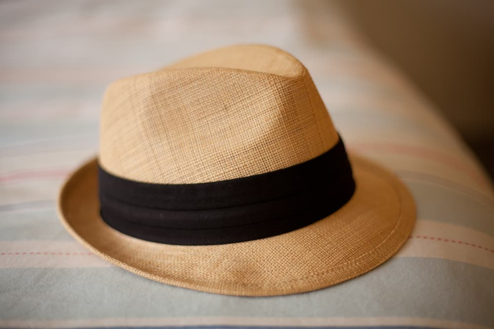 This is a woven straw hat fedora with black band.