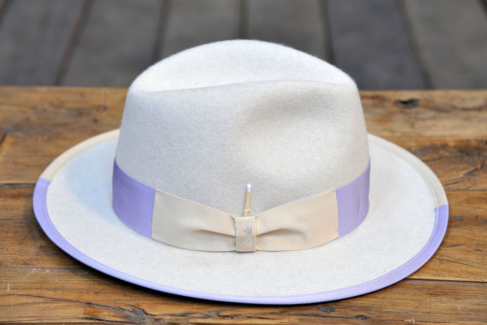 This is a borsalino hat on a table with purple accents.