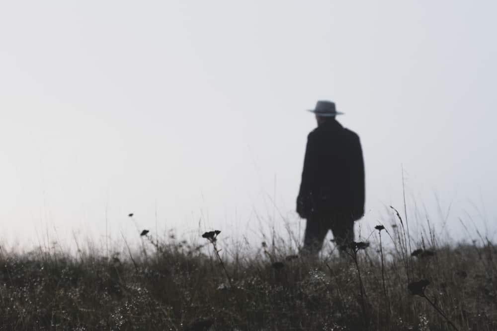 A man walking on a grass field wearing a fedora.