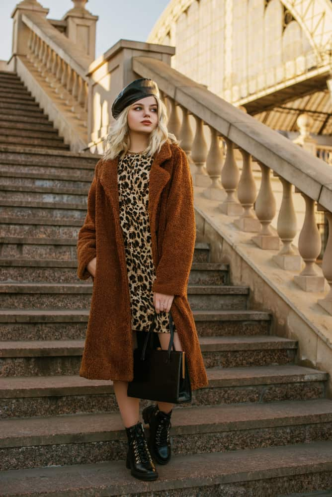 This is a woman wearing a leather beret with her animal print dress.