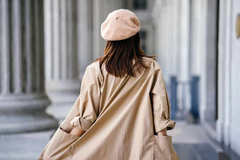 This is a close look at a woman wearing a beige beret with her tan trench coat.