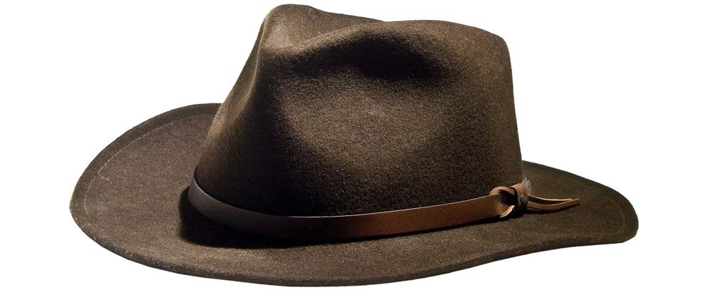 A close look at a brown fedora hat with a brown leather band.