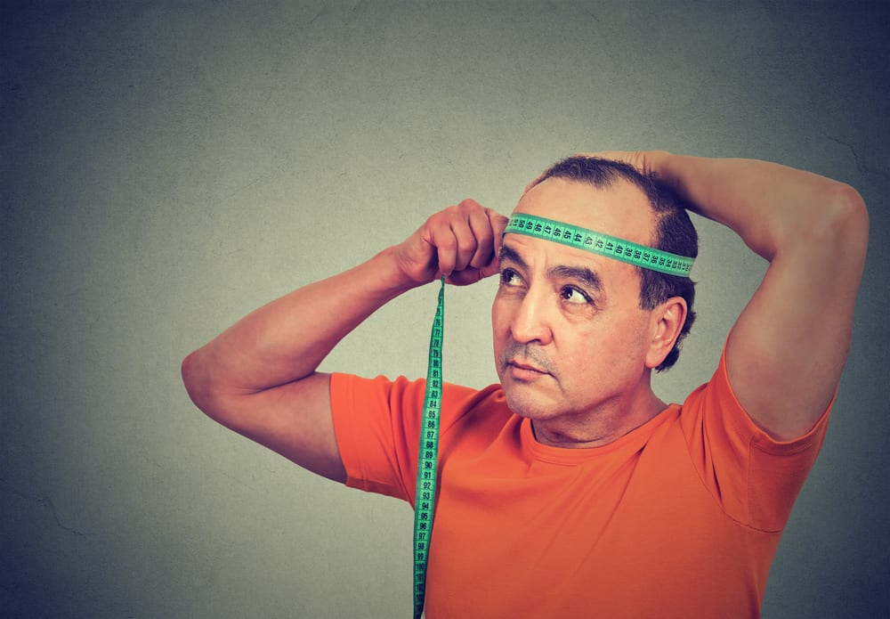 A close look at a man measuring his hat size with a measuring tape.