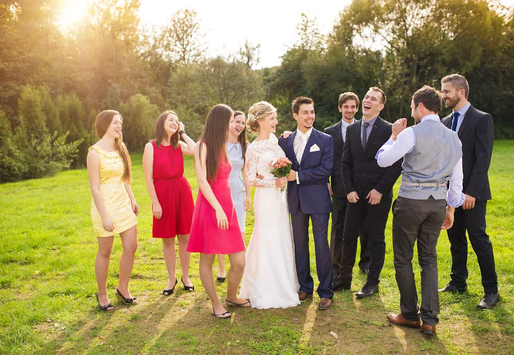A newly wed couple laughing with their friends with the men wearing suits and the women wearing dresses.