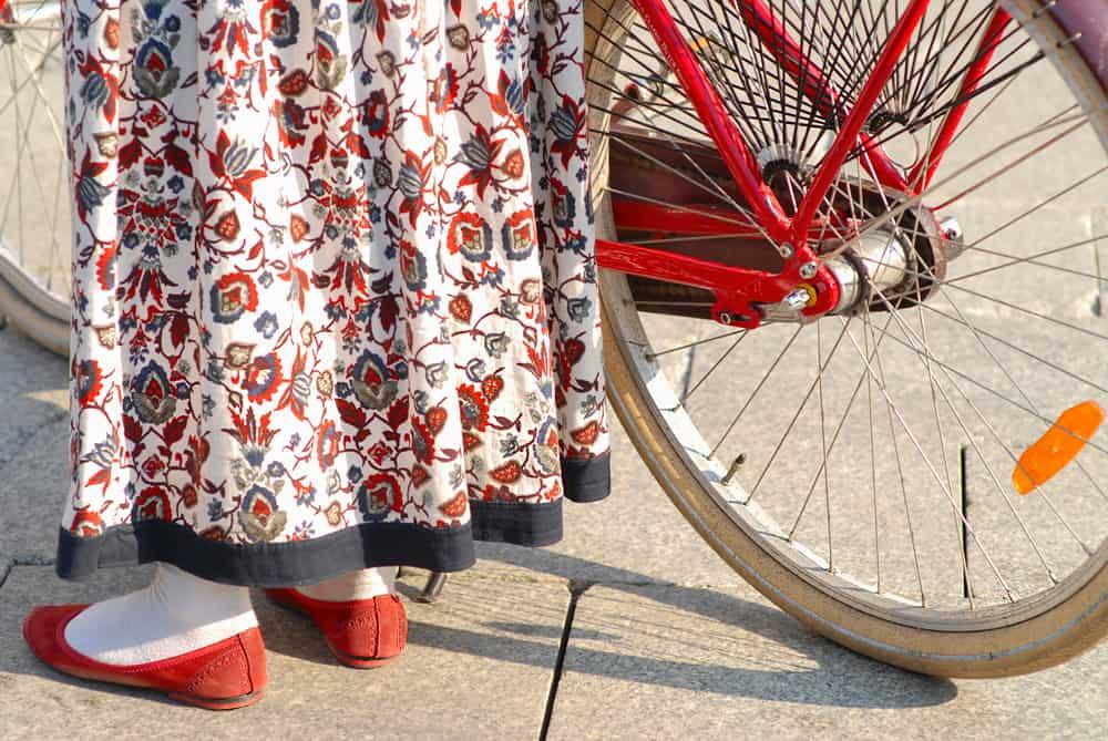 Woman walking her bike while wearing a long floral dress.