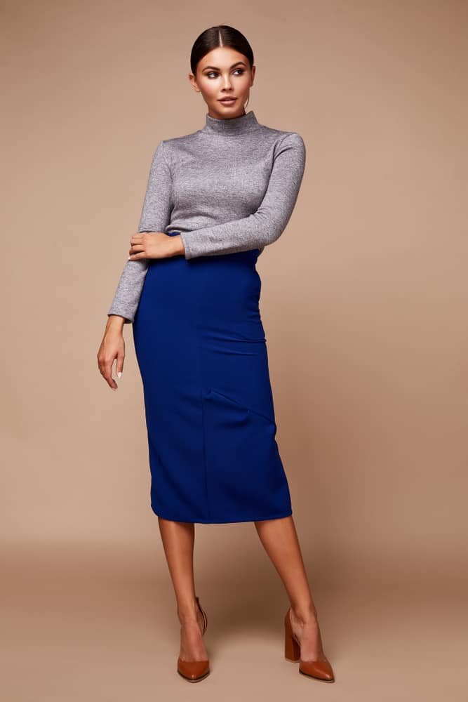 This is a woman wearing a long-sleeve gray shirt and a blue long skirt.