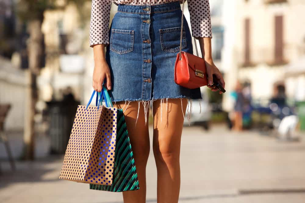 This is a close look at a woman wearing a jean skirt with her patterned blouse.