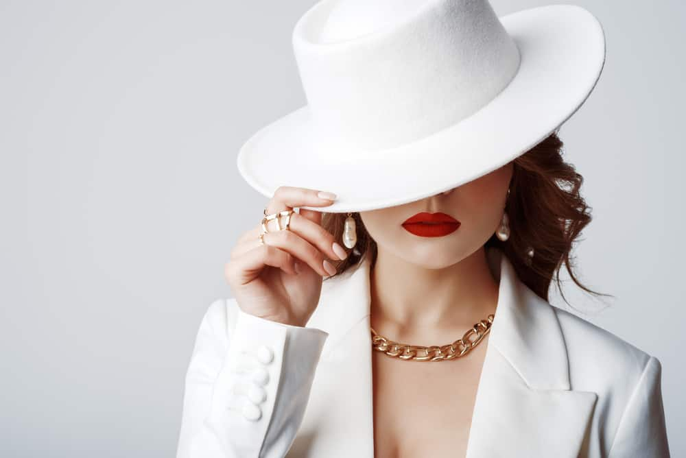 A woman wearing a white suit and matching white fedora.