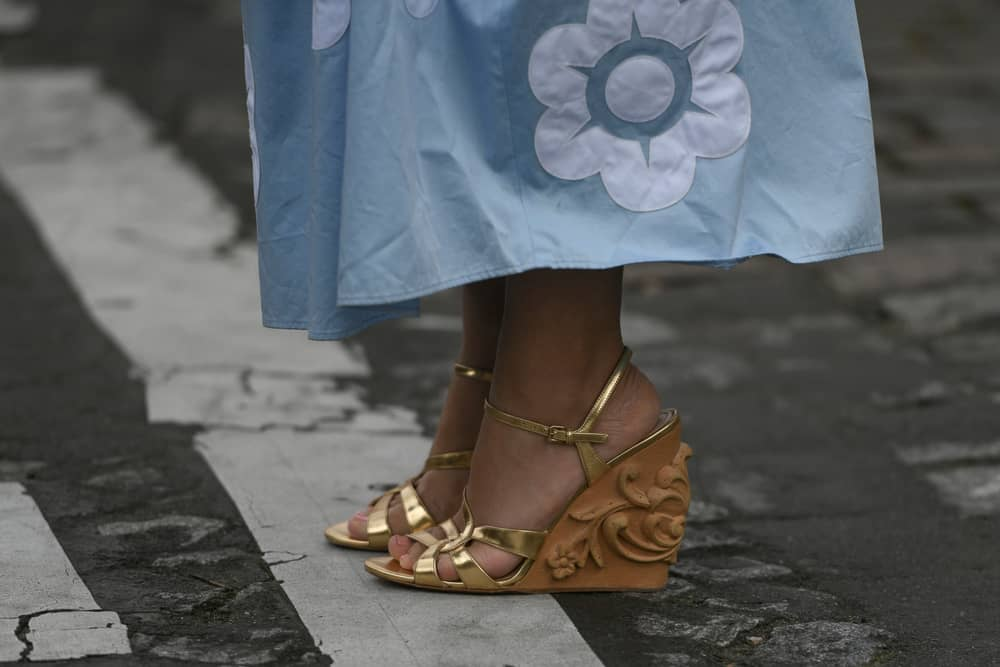A close look at a woman wearing a pair of wedge heels that has golden straps.