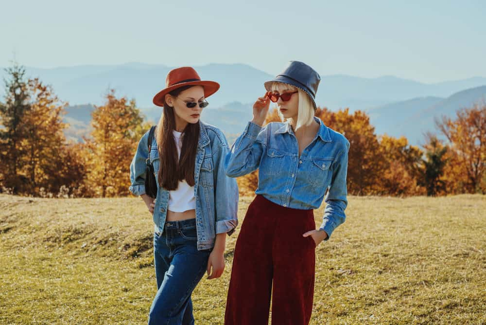 These are two women wearing a fedora and a bucket hat with their denim jackets.