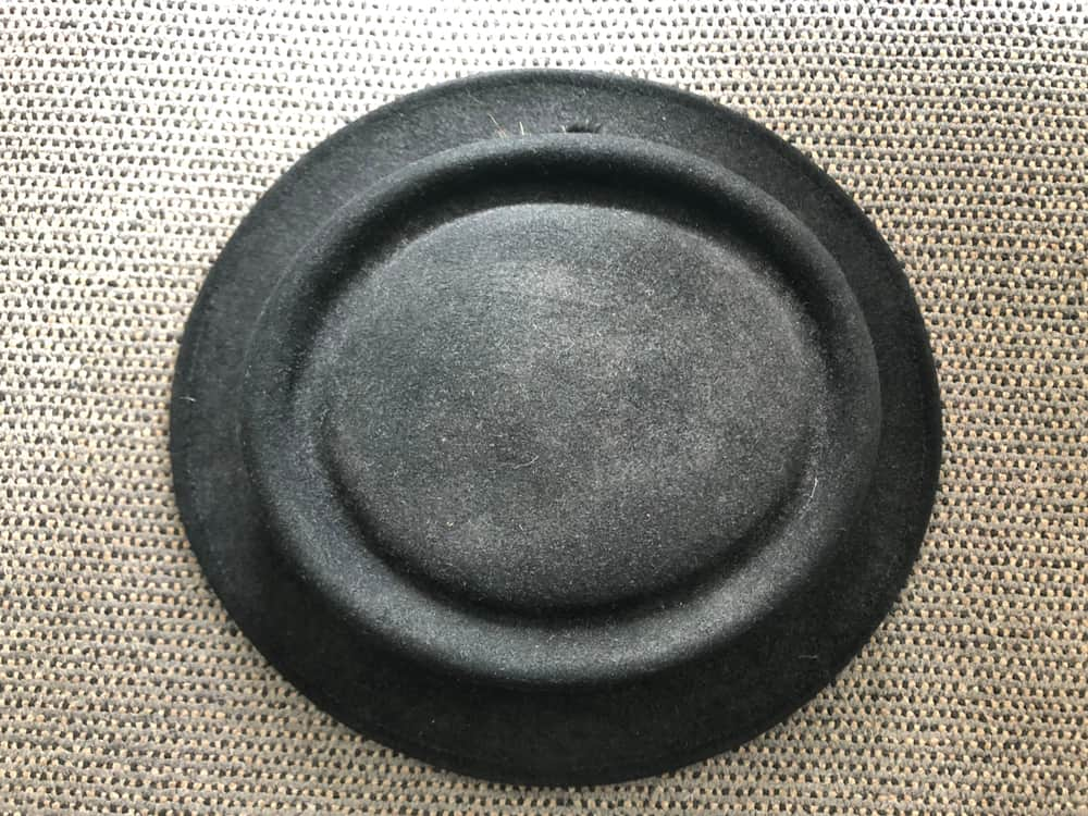 This is a close look at a black pork pie hat on a gray carpet.