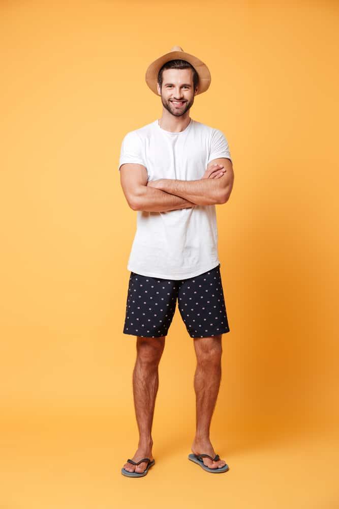 A man wearing casual slip-ons, shorts, shirt and a fedora hat.
