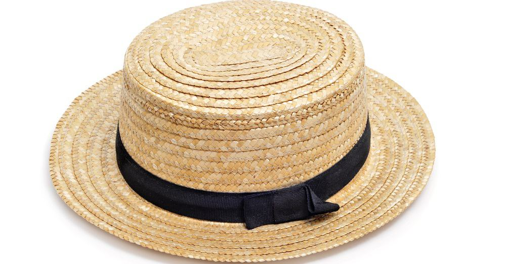 A close look at a straw boater hat that has a thin black band.
