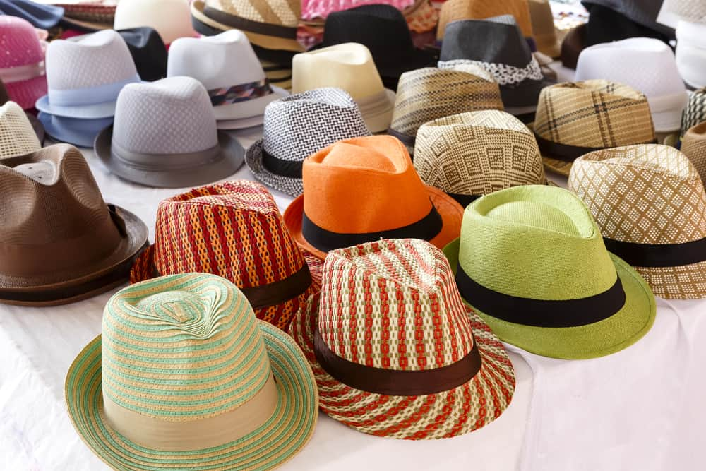 These are various colorful and patterned fedoras on display.