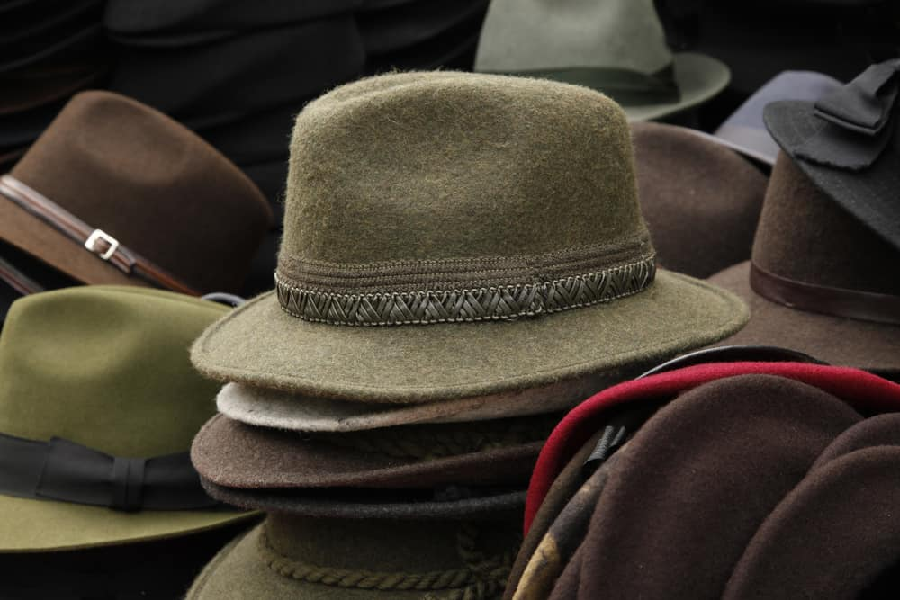 This is a close look at various fedora hats on display at a market.
