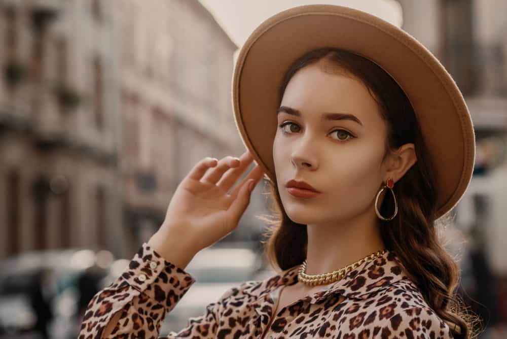 A woman wearing animal print blouse and a wide-brim fedora.