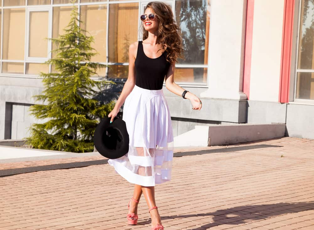 This is a woman wearing a black shirt and a white fabric skirt with sheer parts.