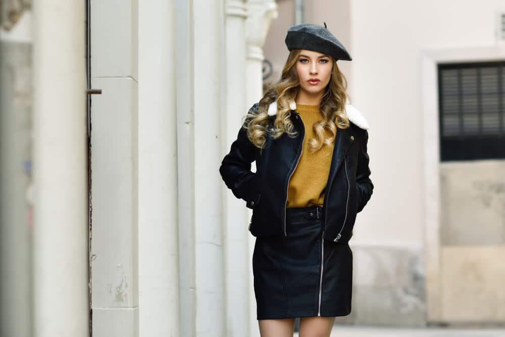 This is a woman wearing a black leather jacket with her black leather skirt.