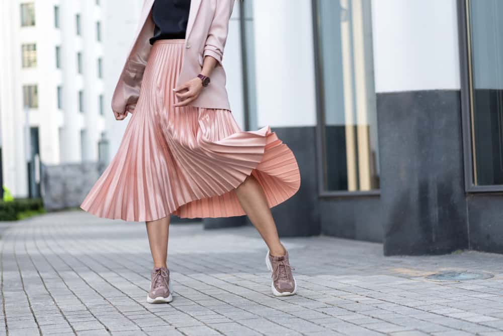 This is a close look at a woman wearing a pink pleated skirt with her sneakers.