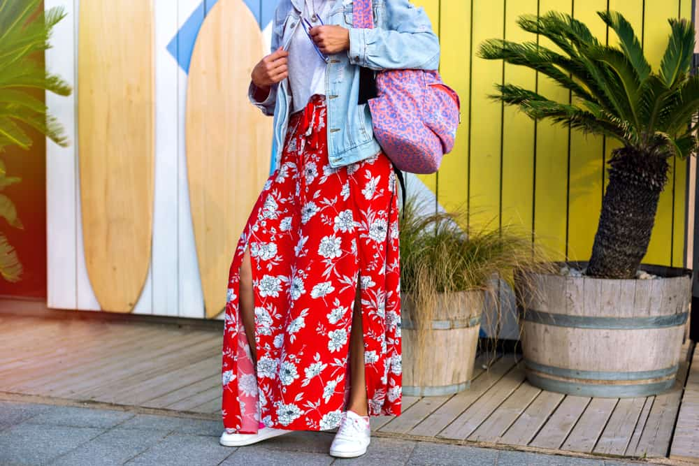 This is a close look at a woman wearing a red floral maxi skirt and a pair of white sneakers.