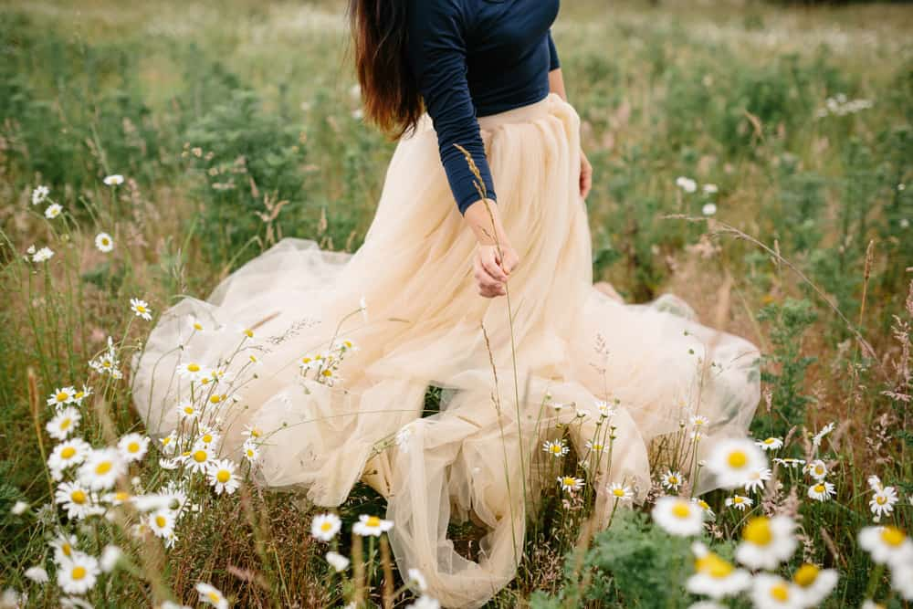 A woman wearing a tulle skirt standing on a field of flowers and grass.