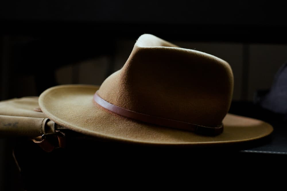 This is a close look at a brown fedora hat with a brown leather satchel.