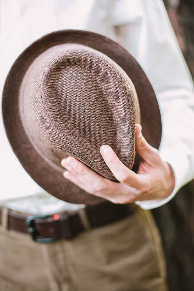 A close look at a man holding a trilby hat.