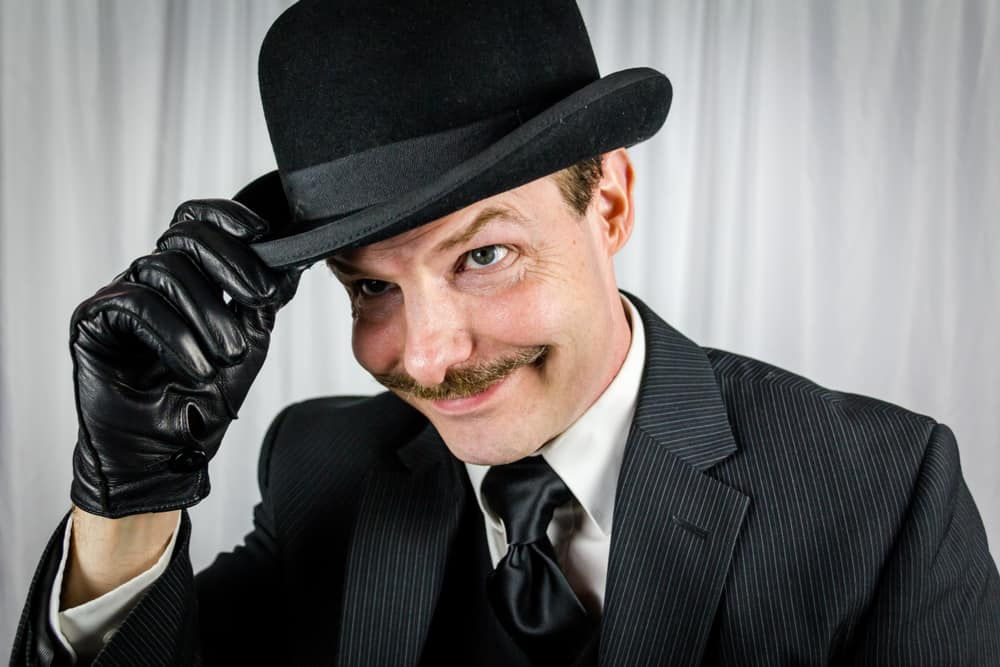A man wearing a black pin-striped suit with a black bowler hat.