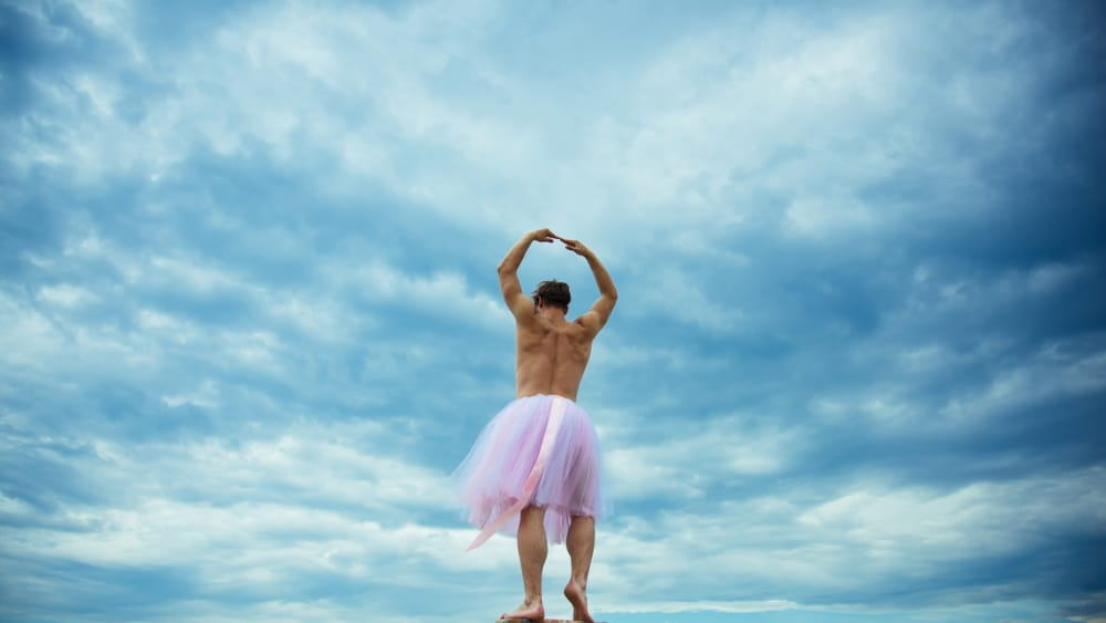 A man wearing a ballerina tutu skirt while dancing.