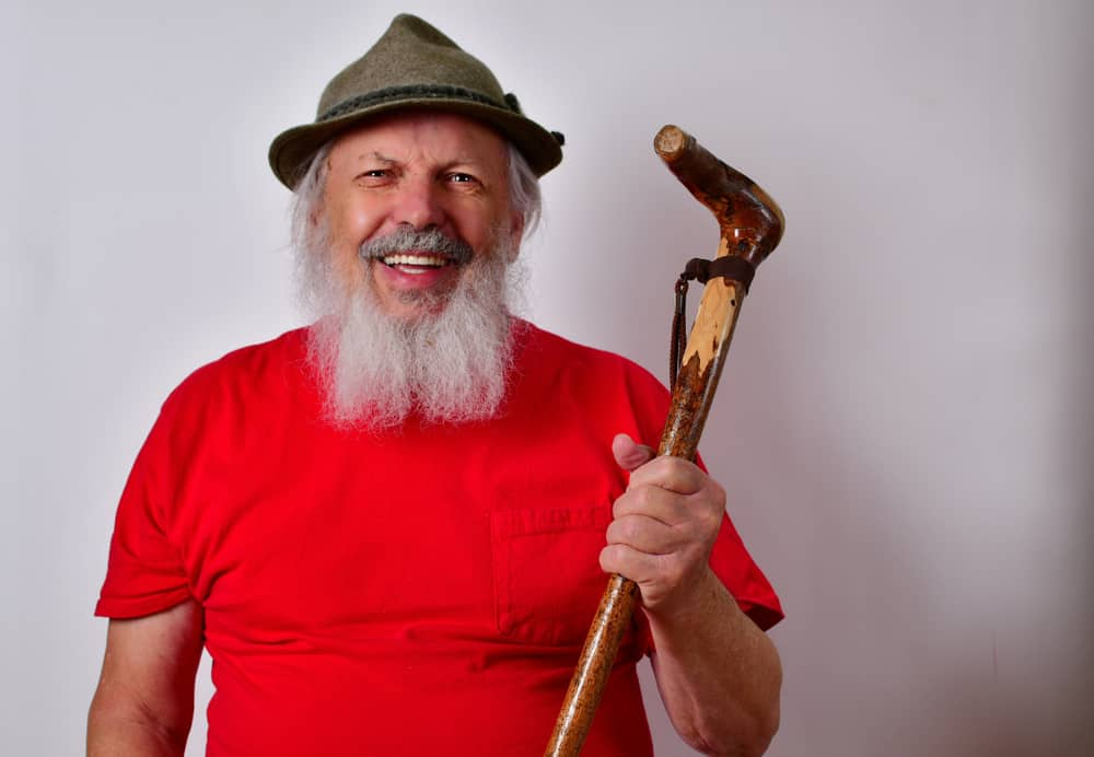 A man with a cane wearing a red shirt and a gray tylorean hat.