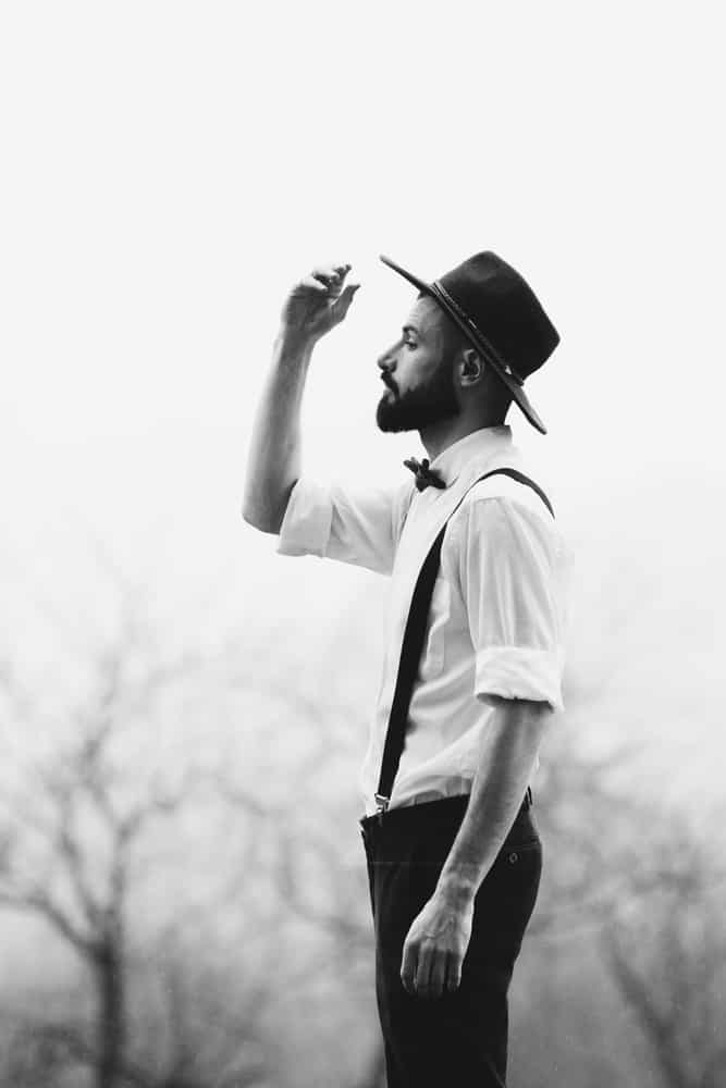 A black and white photo of a man wearing suspenders and a fedora.