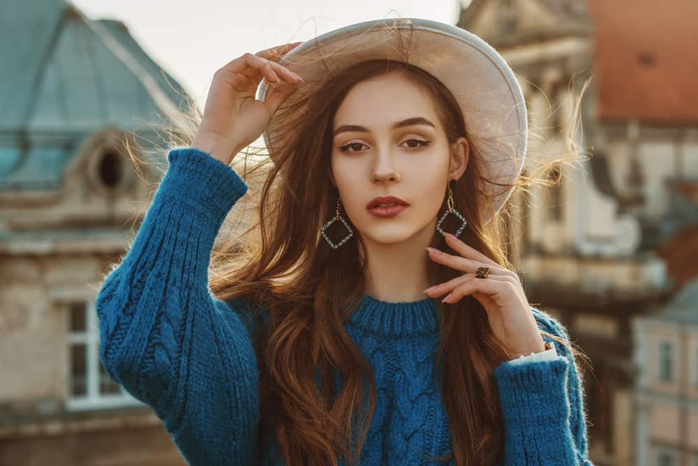 A woman wearing a blue knitted sweater with a fedora.