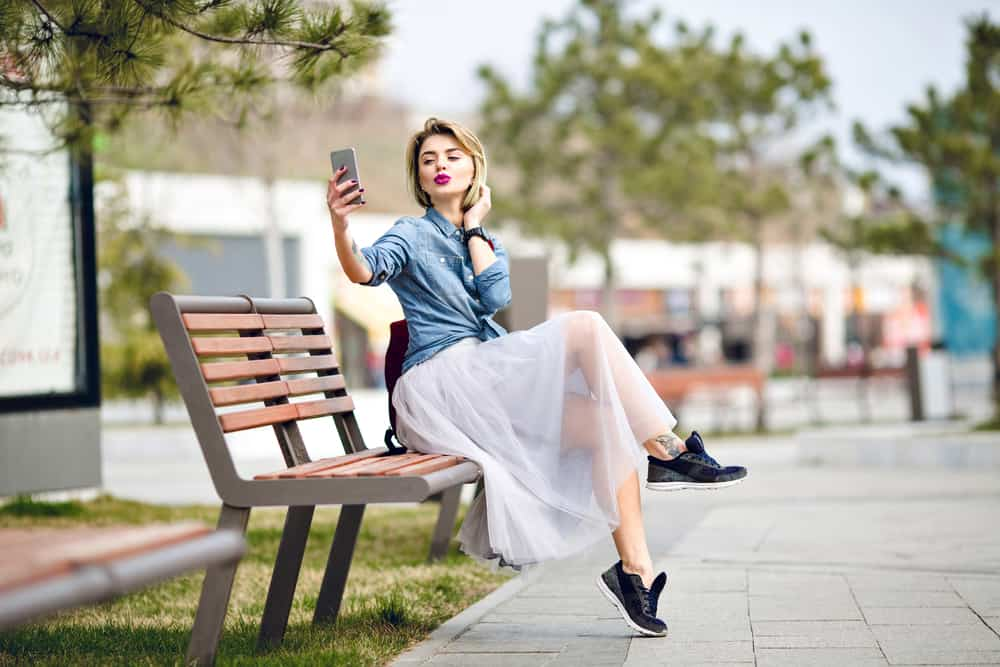 A woman taking a selfie on a park bench wearing a denim top and a white sheer skirt.