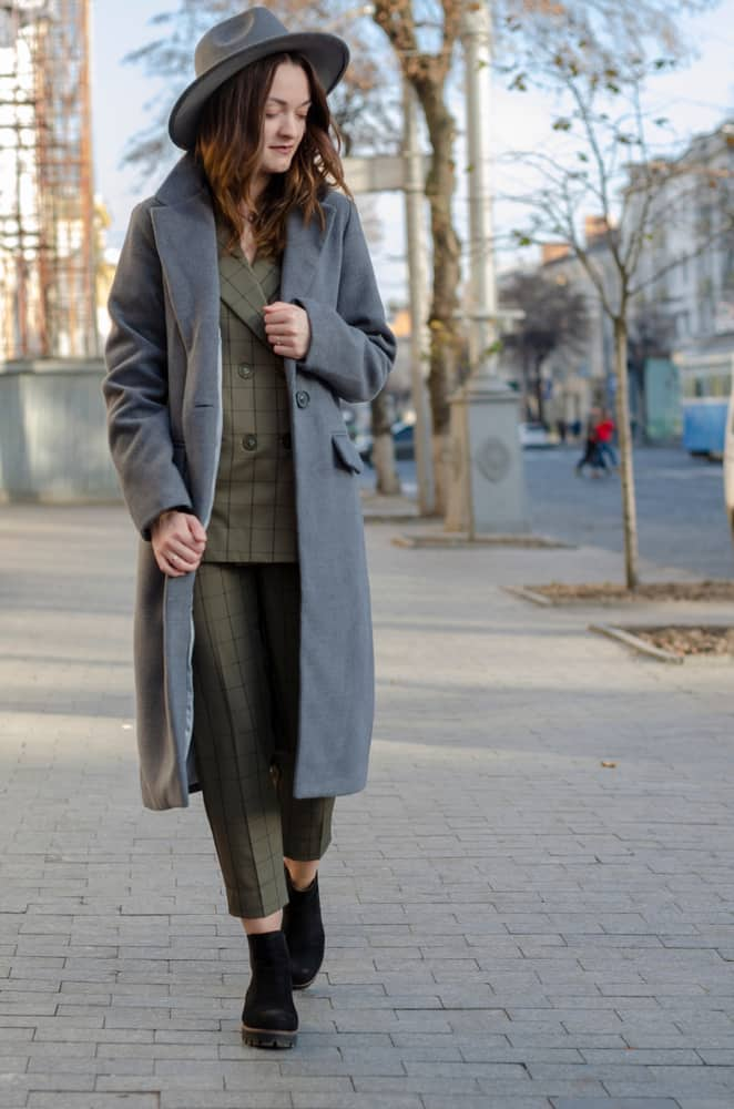 A woman wearing a gray trench coat with her gray fedora.