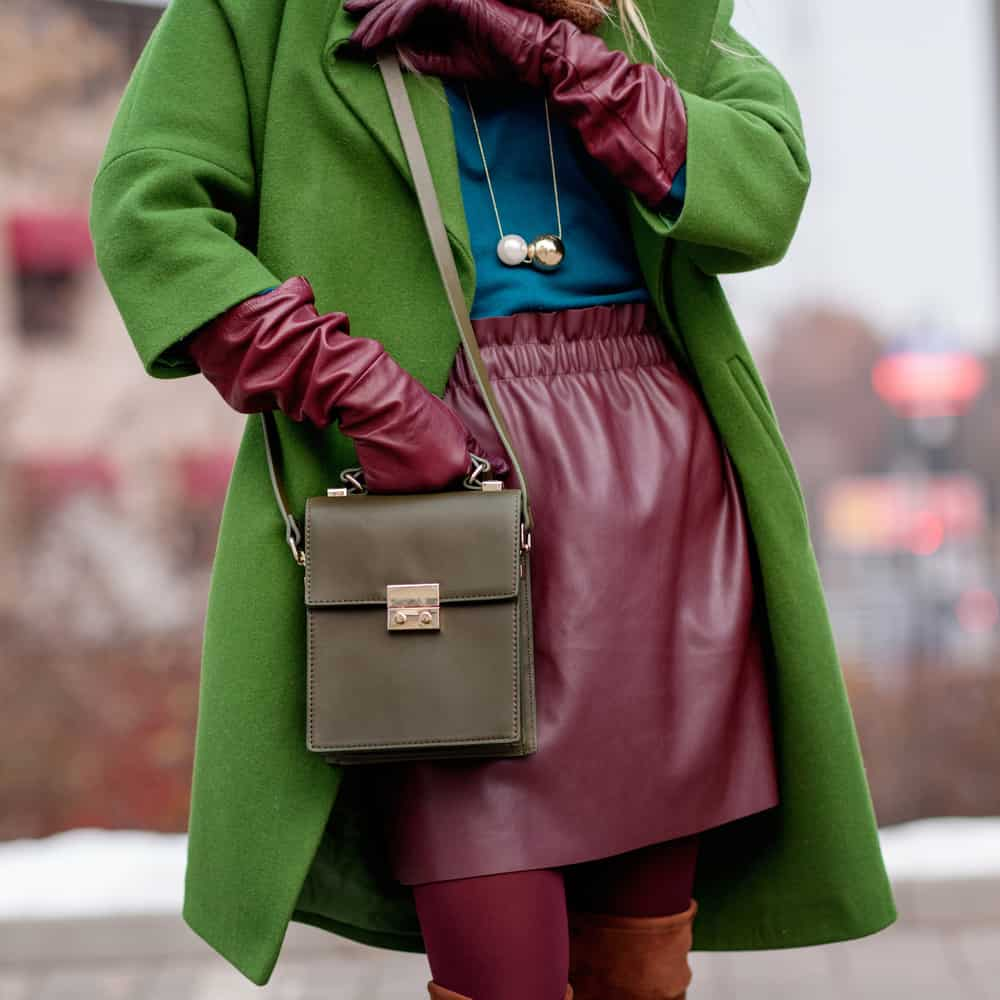 This is a woman wearing a red leather skirt with her green coat.