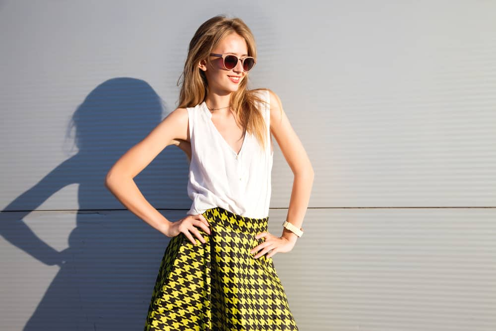This is a woman wearing a white blouse with her patterned yellow skirt.