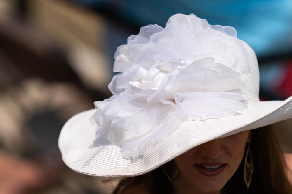 A woman wearing a white derby hat that has a floral embellishment.