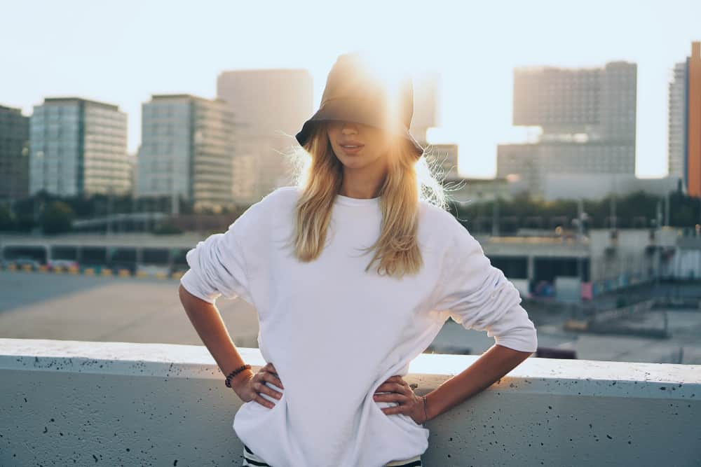This is a woman wearing a white oversized shirt with her bucket hat.