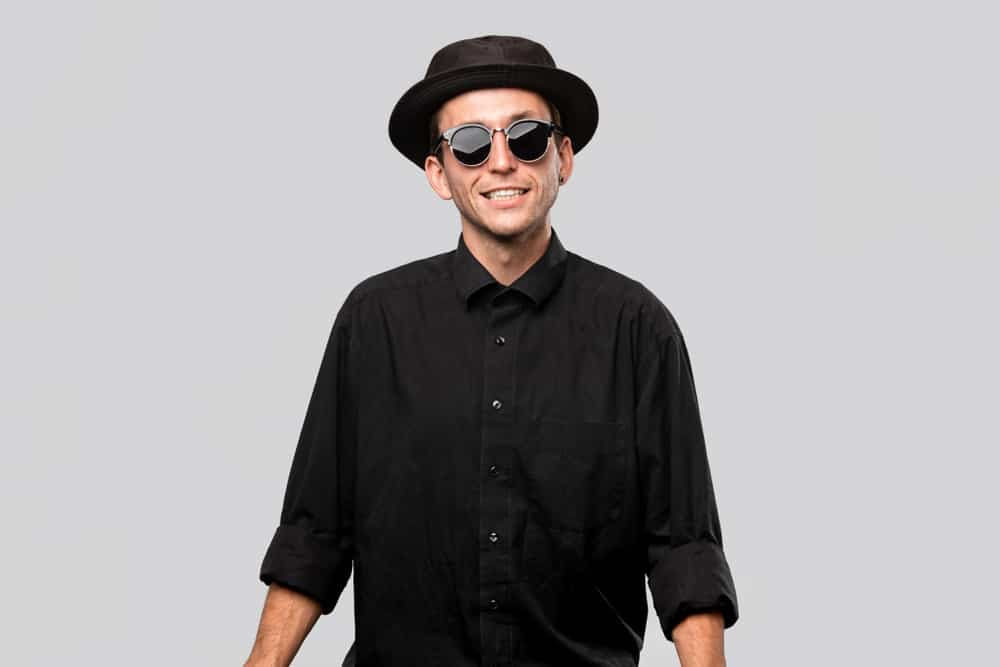 A man wearing a black button shirt with his black pork pie hat and sunglasses.