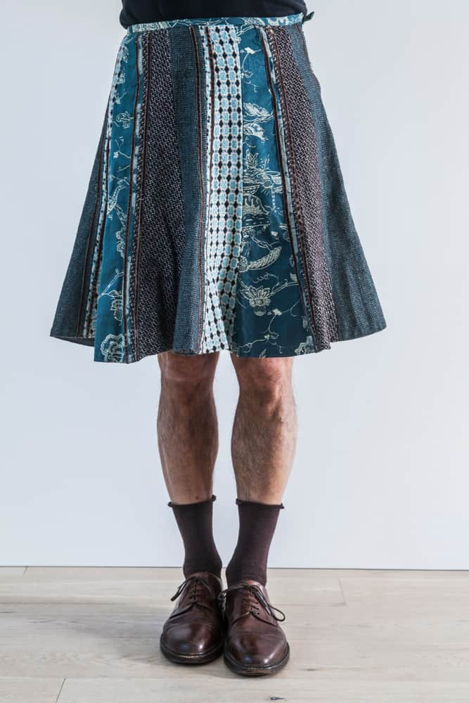 A man wearing a patterned knee-length skirt.
