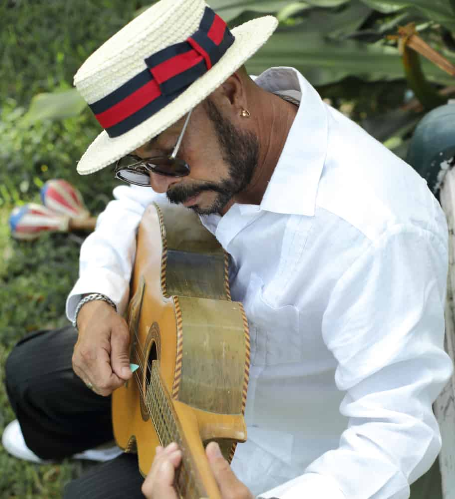 A close look at a man wearing a white boater hat while playing the guitar.