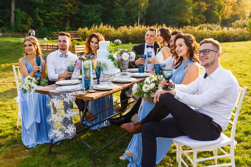 Newlyweds dining on the grass lawn with their groomsmen and bridesmaids who are wearing matching dresses.