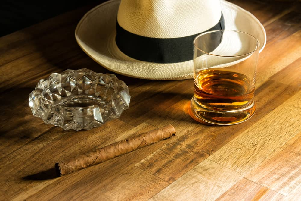 A close look at a Panama hat, a cigar and a glass of rum.