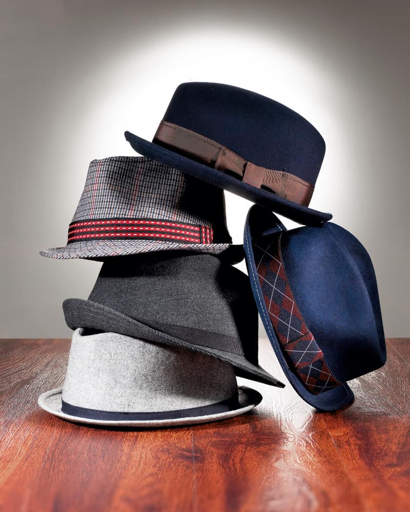 A close look at a stack of fedoras on the floor.