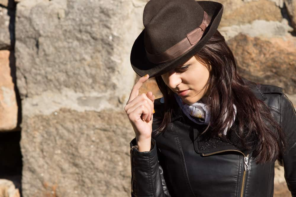 A woman wearing a black rider jacket with her brown fedora hat.