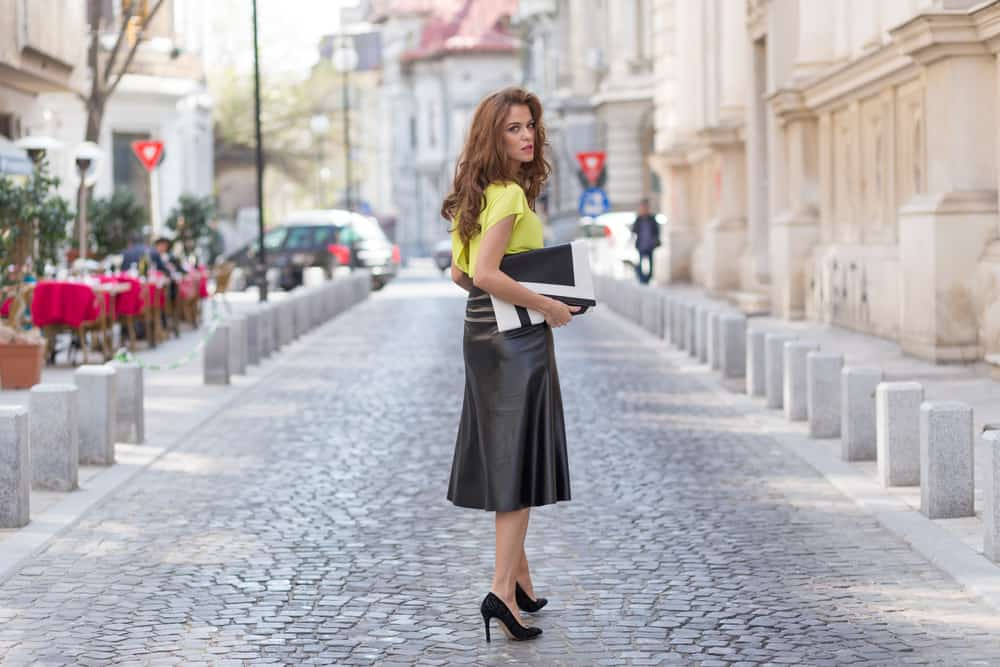 This is a woman wearing a long leather skirt with her yellow blouse.