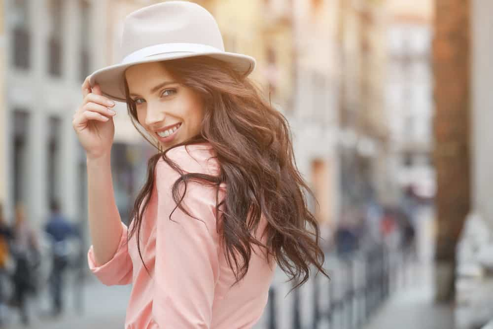 A woman with long wavy hair wearing a fedora and a pink blouse.
