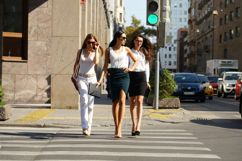 Three women crossing the street wearing various outfits with pants and skirts in varying levels of formality.