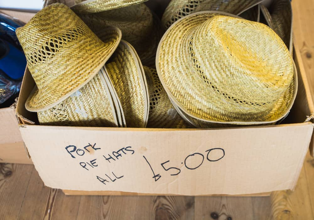 This is a box of woven pork pie hats for sale.